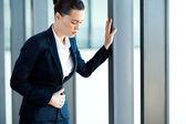 Genç iş kadını ofiste mide ağrısı olması — Stok fotoğraf