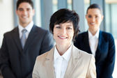 Elegant middle aged businesswoman leader and team — Stock Photo