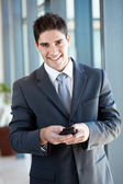 Young businessman using smart phone sending emails — Stock Photo