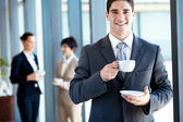 Young businessman having coffee break in office — Stock Photo