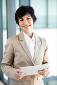 Elegant middle aged businesswoman with tablet computer — Stock Photo