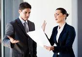 Två unga kollegor argumenterar över pappersarbete i office — Stockfoto