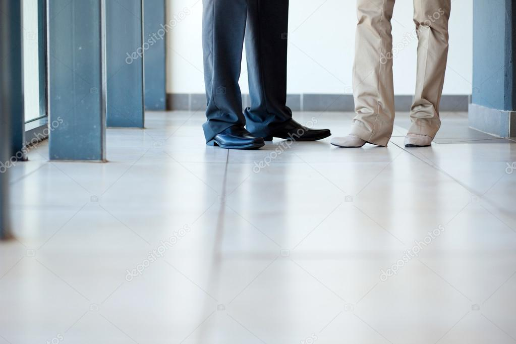 Businessman and businesswoman standing on office floor  Stock Photo #12288121