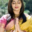 Stock Photo: Young indian woman praying outdoors