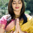 Young indian woman praying outdoors - Stock Photo