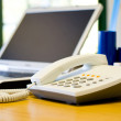 Office desk with telephone and laptop — Stock Photo