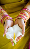 Ndian woman holding flower with both hands — Stock Photo