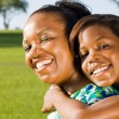 Happy african american mother and daughter piggyback outdoors - Стоковая фотография