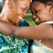 African mother and daughter hugging outdoors — Stock Photo #12392280