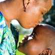 Loving african american mother kissing her son on forehead — Stock Photo