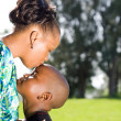 African mother kissing son outdoors — Stock Photo