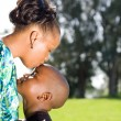 Stock Photo: Africmother kissing son outdoors