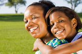 Happy african american mother and daughter piggyback outdoors — Fotografia Stock
