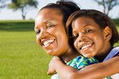 Mutlu afrika kökenli amerikalı anne ve kız açık havada omzunda — Stok fotoğraf