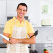 Young man chopping vegetables in kitchen — Stock Photo #12442438