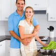 Young woman and husband cooking in kitchen - Lizenzfreies Foto