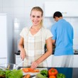 Young woman and husband cooking in kitchen — Stock Photo