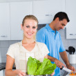 Happy young couple cooking in kitchen — Stock Photo #12442456