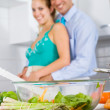 Happy young couple cooking in kitchen — Stock Photo