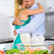 Happy young couple cooking in kitchen — Stock Photo #12442467