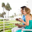 Happy young couple sitting on balcony drinking coffee — Stock Photo