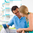 Happy young couple using laptop on balcony — Stok fotoğraf