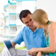 Stock Photo: Happy young couple using laptop on balcony