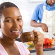 African american woman drinking coffee in kitchen — Stock Photo #12442631