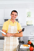 Young man chopping vegetables in kitchen — Stock Photo