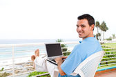 Young man using laptop on balcony — Stock Photo