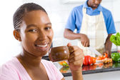 African american woman drinking coffee in kitchen — Stock Photo