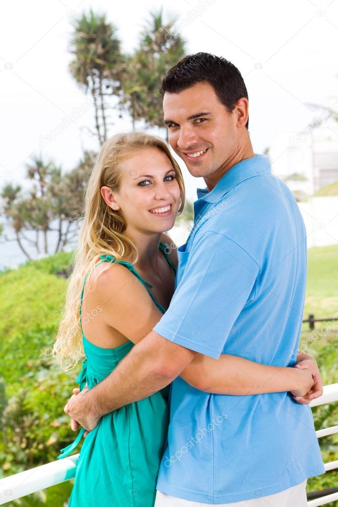 Young happy lovely couple hugging, background is sea view — Stock Photo #12442490