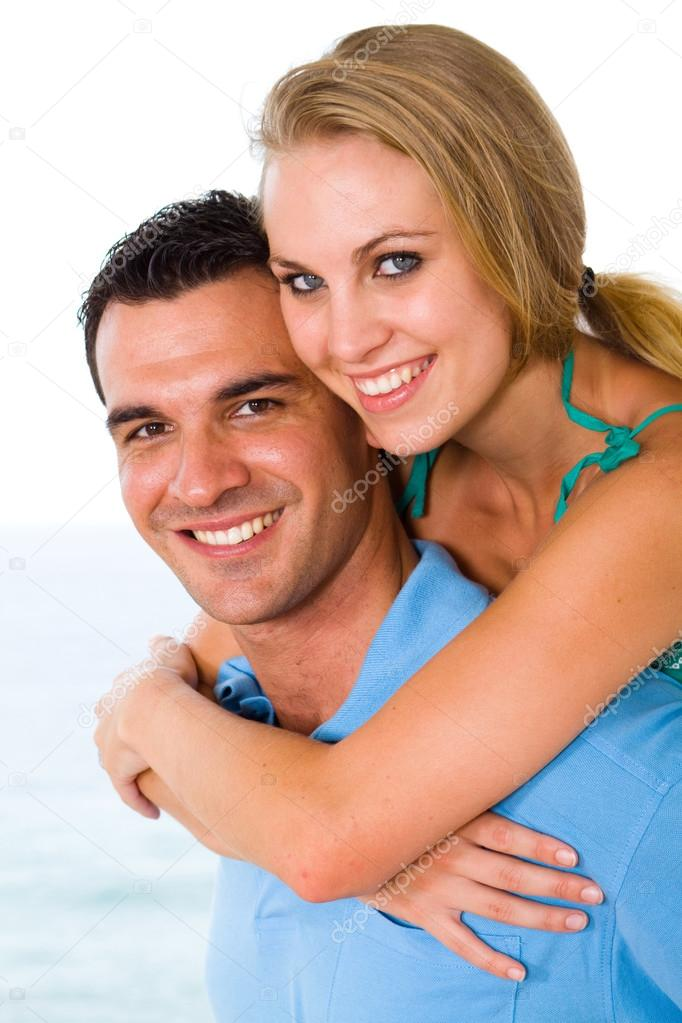 Happy young couple piggyback with beautiful sea view behind — Stock Photo #12442496