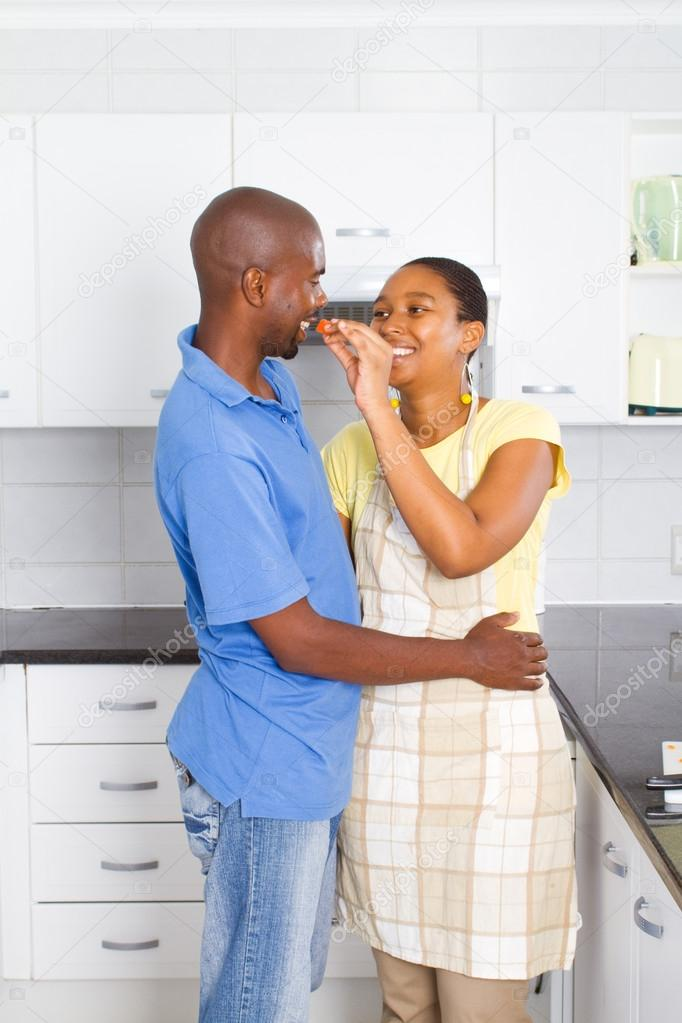 Happy young african couple taste food in kitchen — Stock Photo #12442621