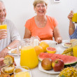Stock Photo: Happy friends having breakfast together