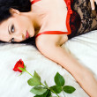 Sexy woman in lingerie holding rose in bed — Stock Photo #12485735