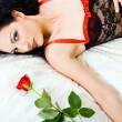 mujer sexy en ropa interior con color de rosa en la cama — Foto de Stock