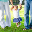 Cute baby girl walking with parents — Stock Photo