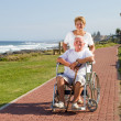 Senior man being pushed on wheelchair by his wife — Stock Photo