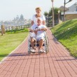 Senior woman pushing her disabled husband - Stock Photo