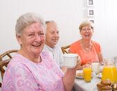 Happy senior friends having breakfast — Stock Photo