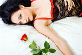 Sexy woman in lingerie holding rose in bed — Stock Photo
