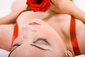 Glamor woman with rose in bed — Stock Photo