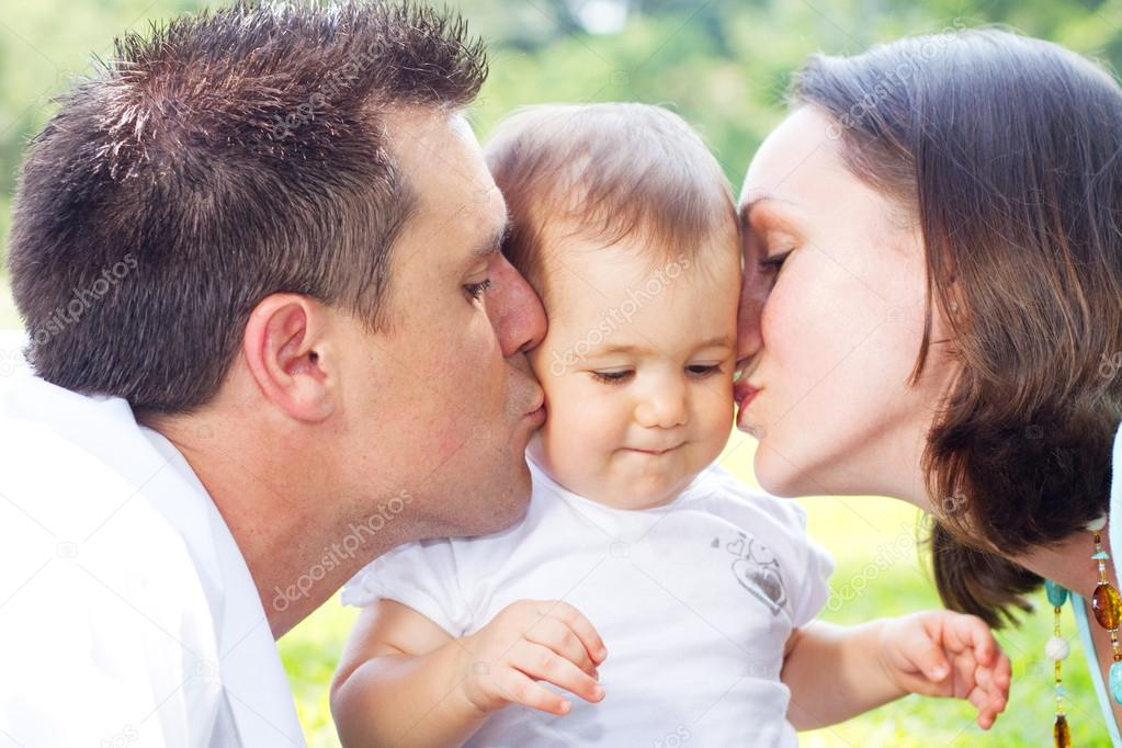 Parents kissing baby girl outdoors — Zdjęcie stockowe #12485901