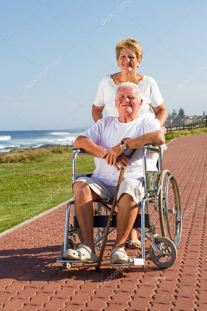 Happy senior wife push husband on wheelchair at beach — Stock Photo #12485935