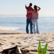 Young couple relaxing on beach, focus on bonfire and beer bottle - Stock Photo