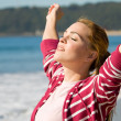 Spiritual woman with arms open wide on beach — Stock Photo