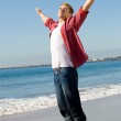 Majestic man with arms outstretched on beach — Stock Photo