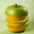 Mixed apple and orange slices on green — Stock Photo