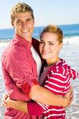 Pareja joven abrazos en la playa — Foto de Stock